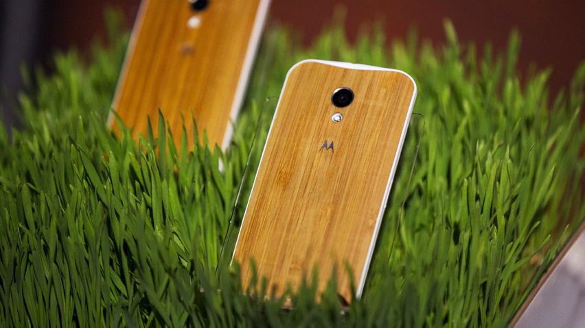 Phones with wooden backs on them rest in a display at a launch event for Motorola's new Moto X phone in New York
